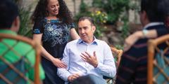 Michael Kuenzle sitter i en stol og snakker med noen venner, og kona hans, Eugenia, står ved siden av ham.