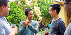 Mario Antúnez using Honduras Sign Language (LESHO) to communicate with three brothers at a social gathering.