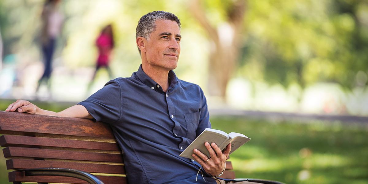 Um homem que está lidando com pensamentos suicidas senta-se no banco do parque, segura uma Bíblia aberta e medita