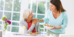 An adult daughter lovingly brings food to her elderly mother