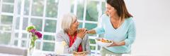 Một người con gái ân cần đưa món ăn cho mẹ lớn tuổi