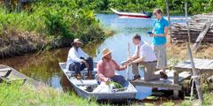 Małżeństwo usługujące na terenie zpotrzebami dzieli się dobrą nowiną zBiblii zdwoma mężczyznami na łodzi