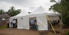 Ihmisiä yleisökokouksessa, joka pidettiin metsään pystytetyssä suuressa teltassa.