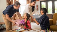 Um pai e uma mãe surpreendem os seus filhos com presentes envolvidos em papel de embrulho.