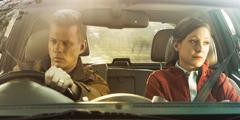 車に乗った夫婦が不機嫌そうに窓の外を眺めている。