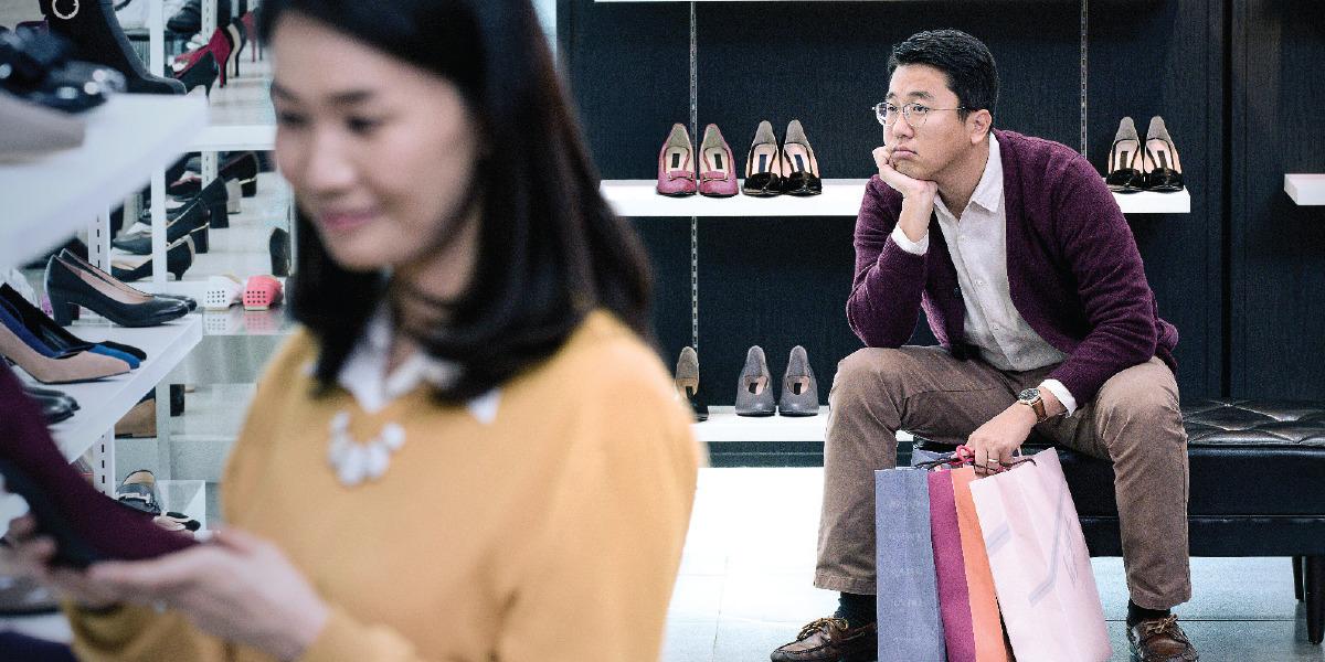 Un esposo está impaciente mientras espera a su esposa, que está comprando zapatos
