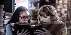 Two teenage girls look at an old book that features the occult