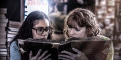 Kaks teismelist tüdrukut uurivad okultistlikku raamatut