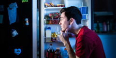 A young man decides which foods to eat from a refrigerator
