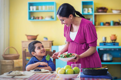 A pregnant woman serves her little boy and herself a healthy meal