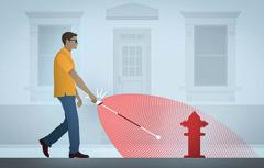 Un uomo cieco che cammina usando un bastone per ciechi elettronico. Grazie all'ecolocalizzazione il bastone lo avverte che c'è un idrante davanti a lui.