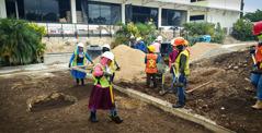 Uma equipe de irmãos e irmãs preparando o solo do jardim do RTO.