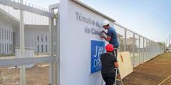 Voluntarios de construcción colocando el nuevo letrero en la entrada de la sucursal de Camerún.