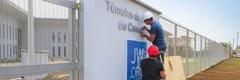Stavební pracovníci pripevňujú nápis na múr pri bráne novej pobočky