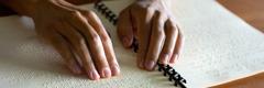 Τυφλή γυναίκα διαβάζει με τα δάχτυλά της μια έκδοση στην Μπράιγ.